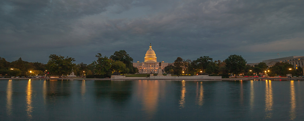 The Capitol building at dusk, lights reflecting on the Capitol lake